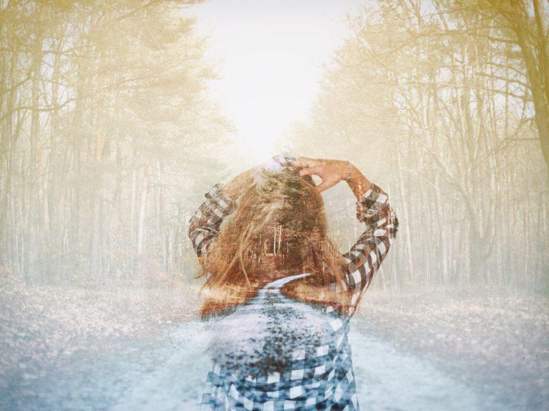 Eine Frau steht im Bild eines Waldes