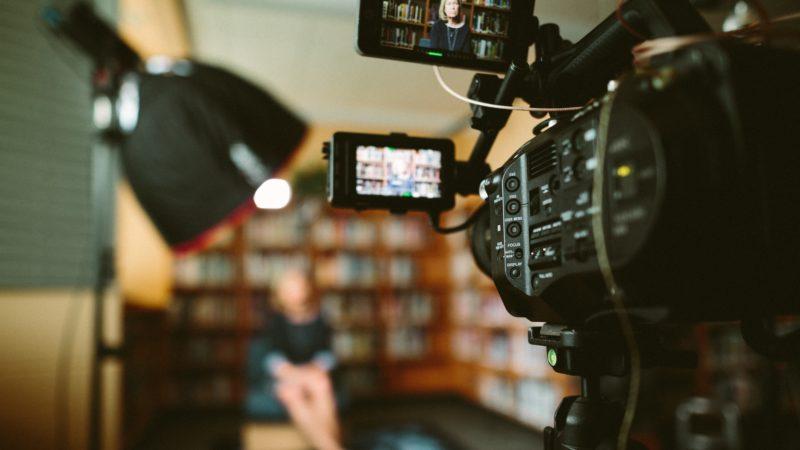 videografie videokamera mit frau vor buecherregal