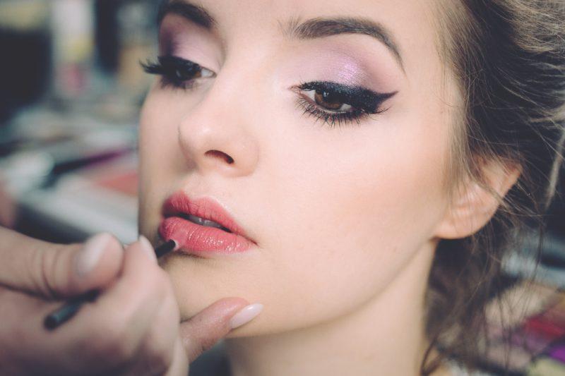 model wird an den lippen geschminkt
