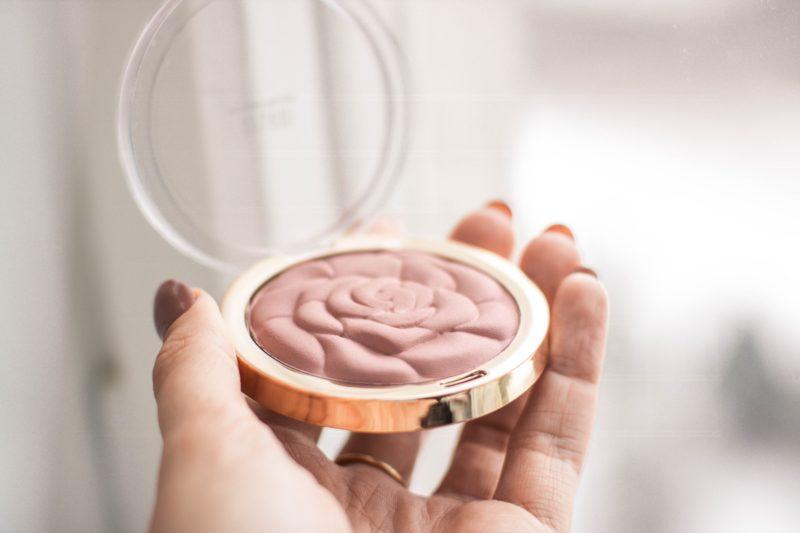 eine hand hält puder make-up
