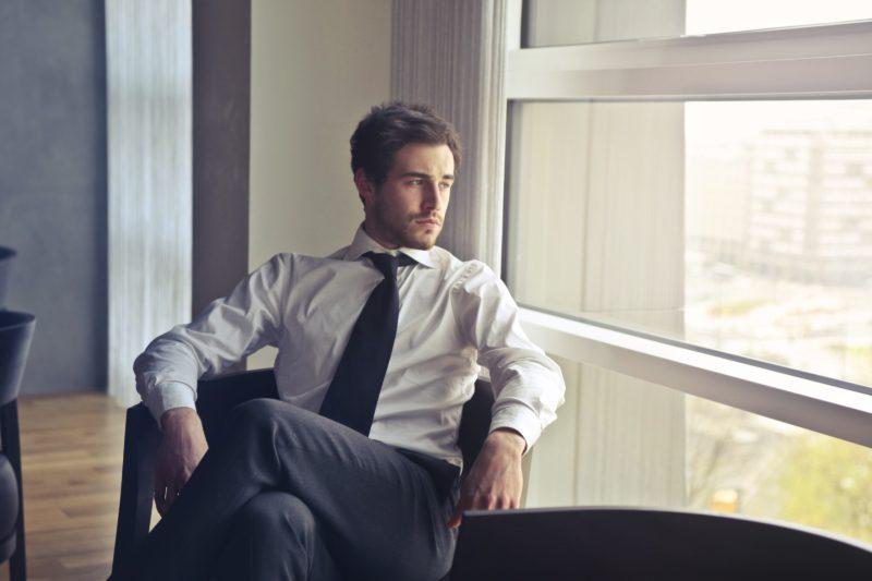 mann mit anzug und krawatte sitzt vor dem fenster