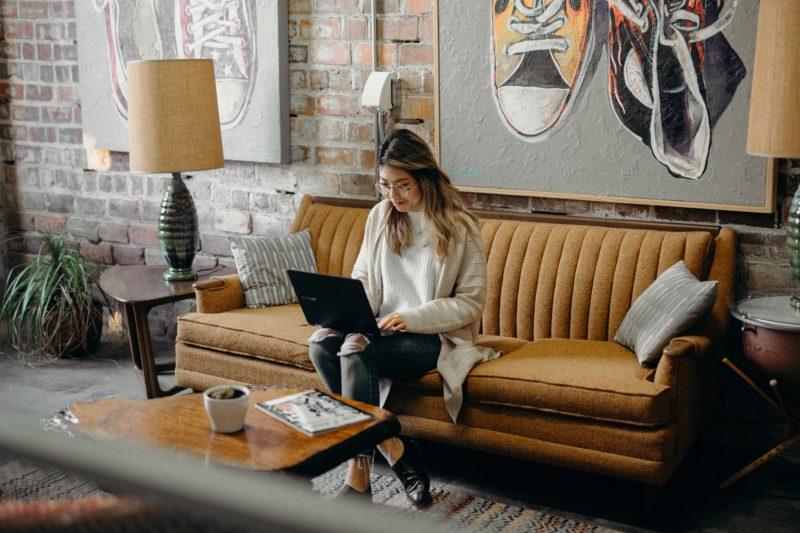 frau sitzt auf dem sofa vor ihrem laptop und posiert als katalog model