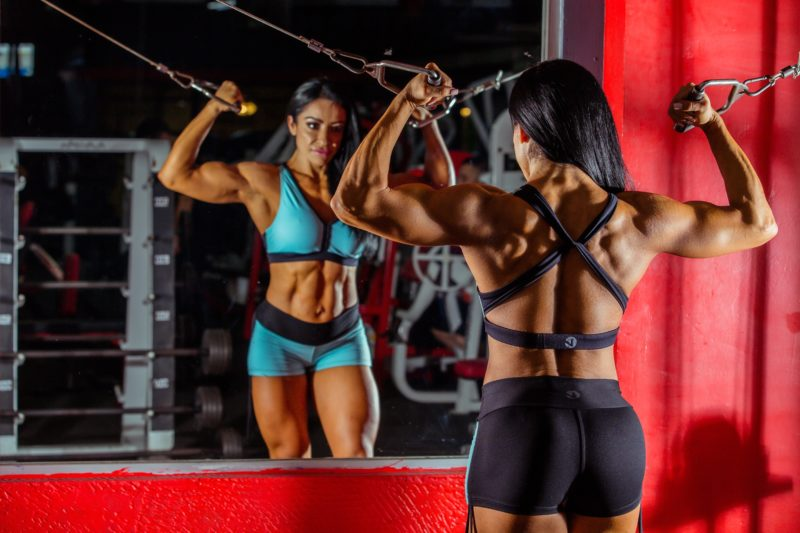 muskuloese frau posiert vor dem spiegel