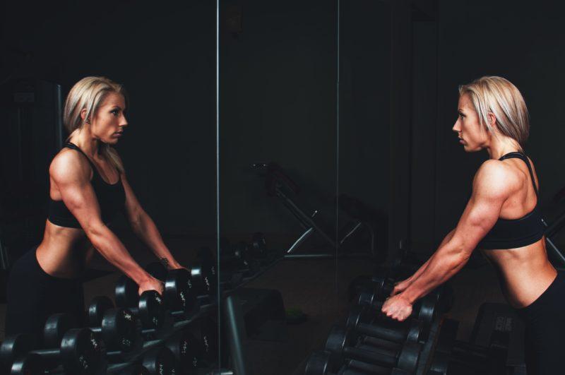fitness model posiert vor einem spiegel mit hanteln