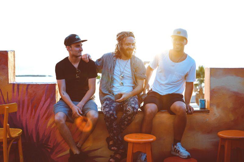 gegenlicht drei männer sitzen auf einer bank