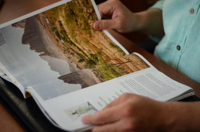 person liest ein magazin mit einem landschaftsfoto