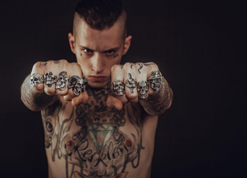 mann mit tattoos ballt faust