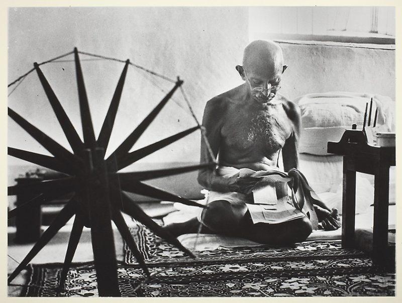 gandhi sitzt auf dem boden vor einem spinnrad