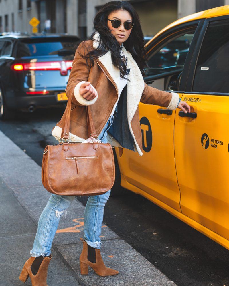 frau steigt in taxi mit handtasche und sonnenbrille