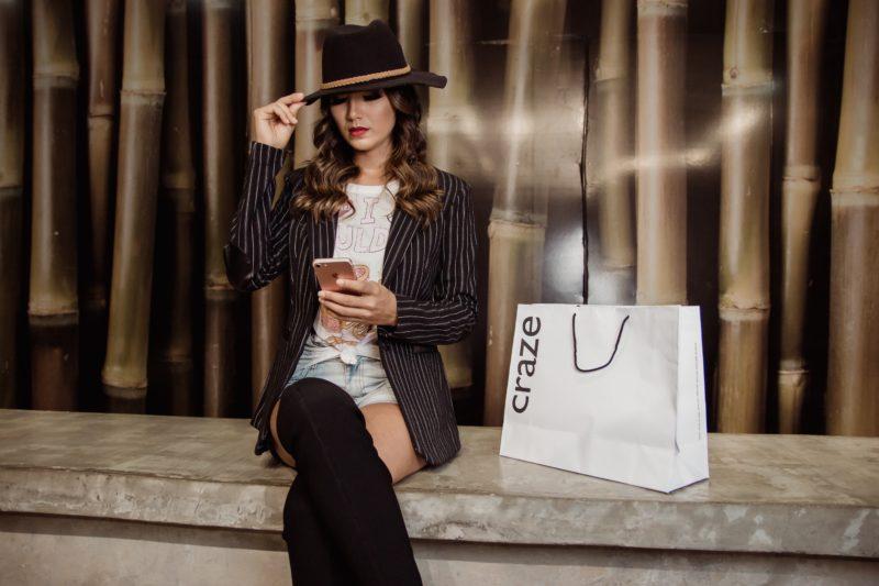 model sitzt mit telefon in der hand und ihren hut haltend