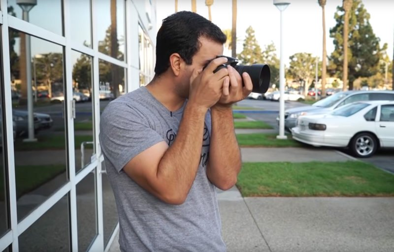 Kamera mit schwerem Objektiv halten