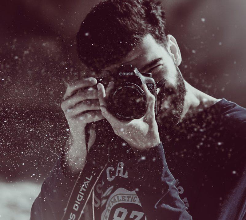 dokumentarfotografie mann mit kamera am fotografieren laechelt