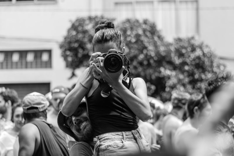 frau mit kamera wird hochgehoben um zu fotografieren