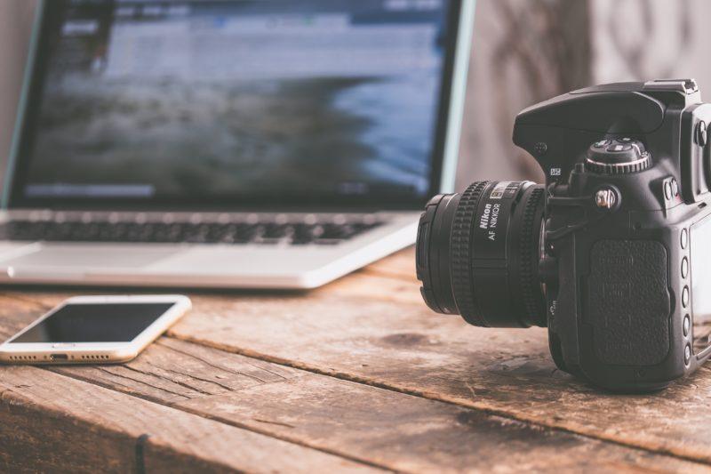 laptop mit kamera und smartphone auf einem holztisch