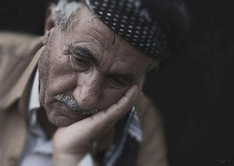 dokumentarfotografie eines alten mannes der den kopf auf seiner hand stuetzt