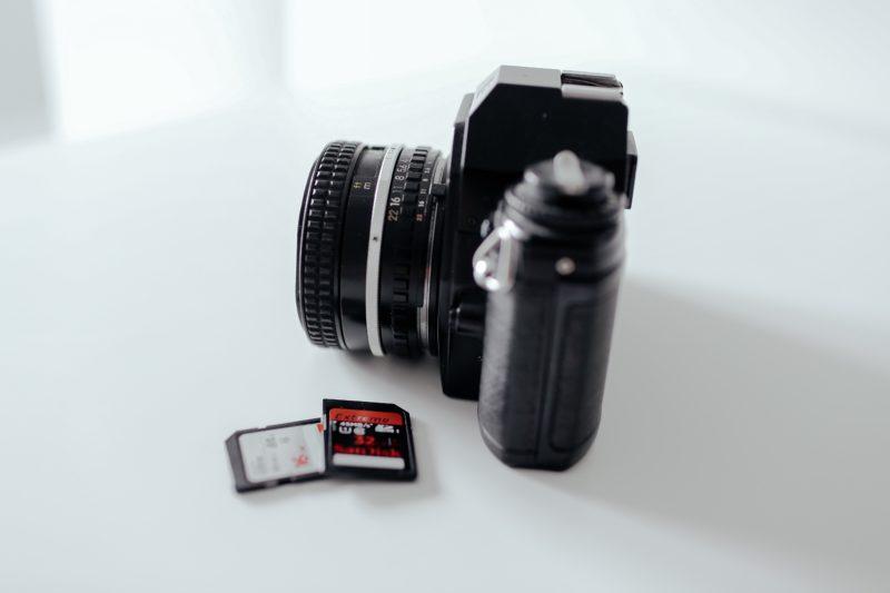 zwei sd cards liegend neben einer kamera