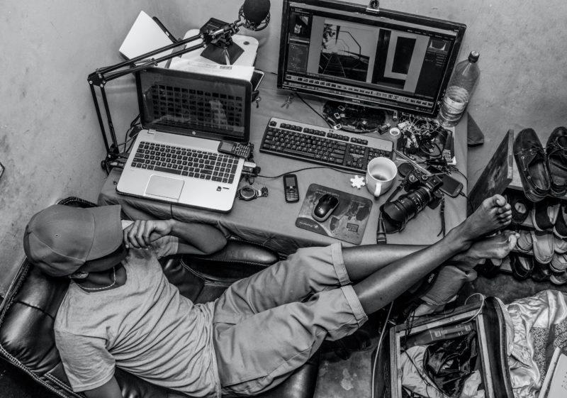 mann sitzt in buero mit computer, laptop, telefon und kamera auf dem tisch