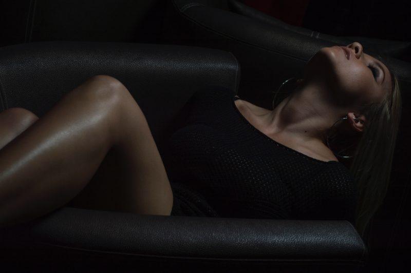 frau posiert erotisch auf einem sessel