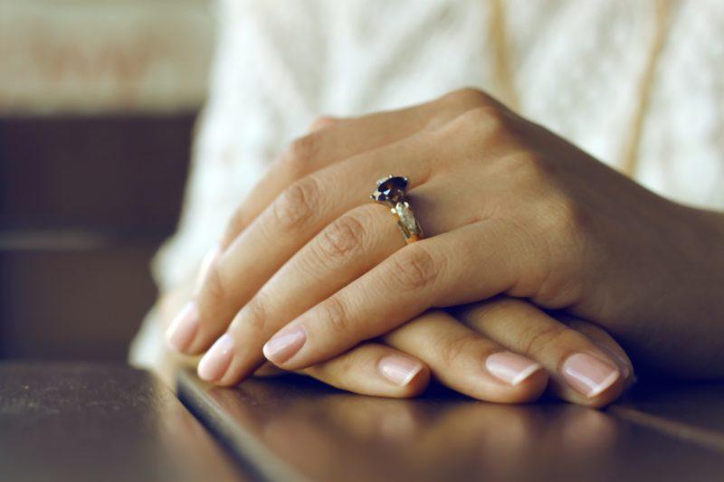 haende uebereinandergelegt auf dem tisch mit ring am finger