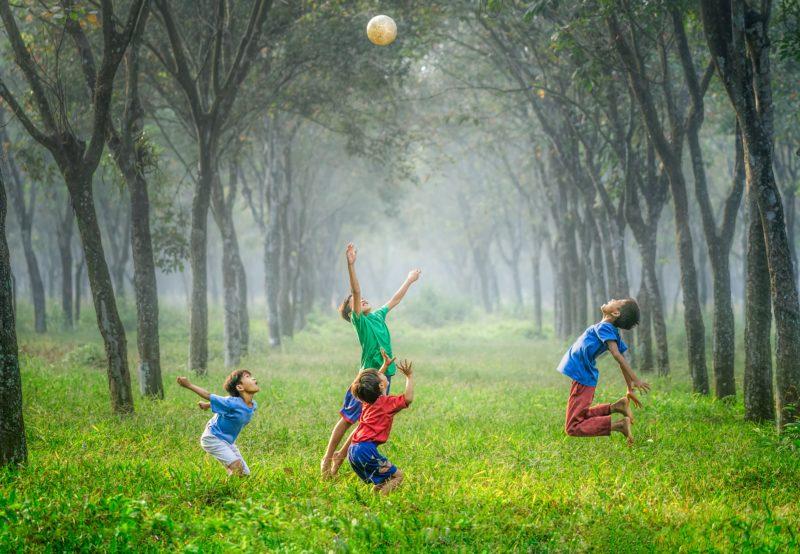 vier jungen spielen in einer allee fussball