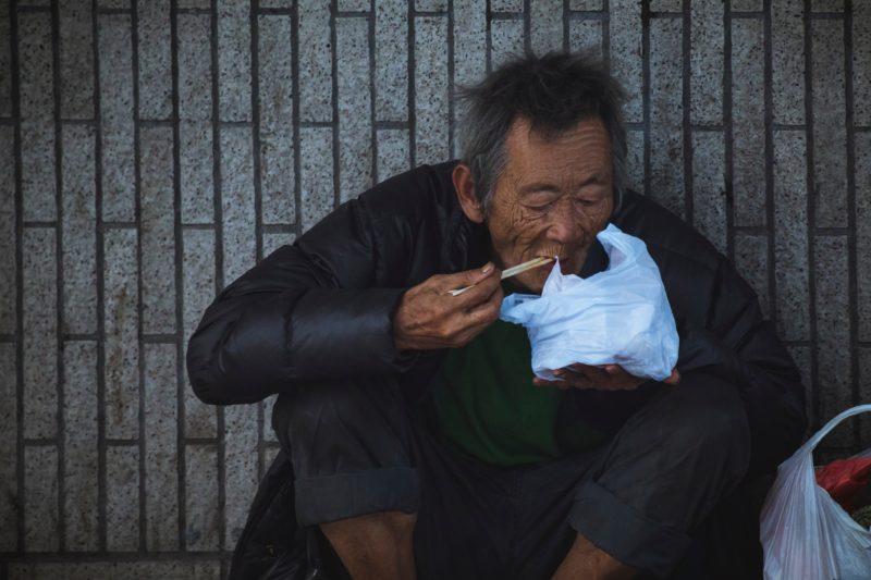 spontanes bild eines essenden mannes auf der strasse