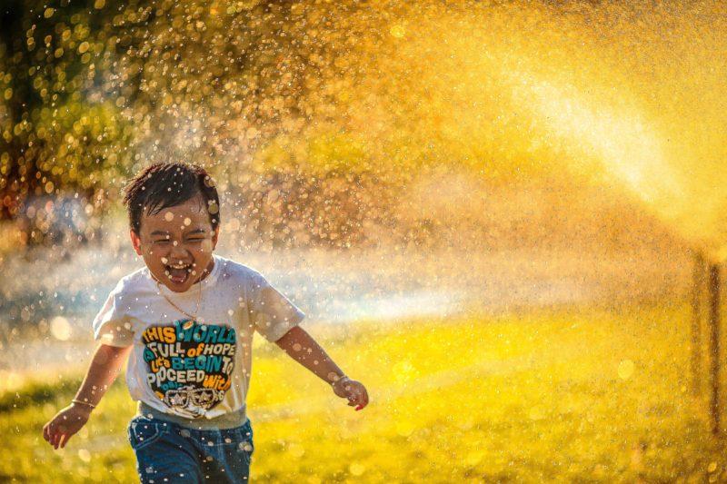 inszenierte fotografie: kleiner junge rennt durch sprinkleranlage
