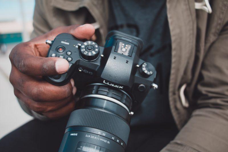 mann haelt kamera in einer hand