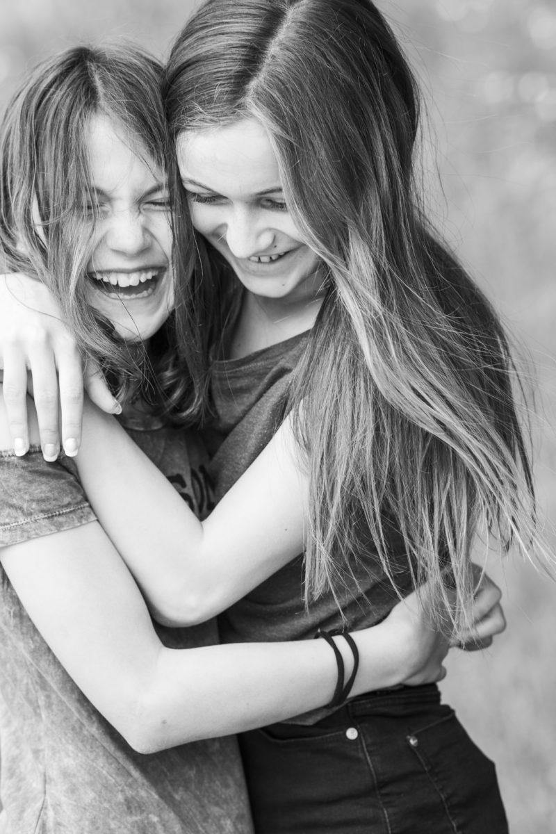 jugendliche freundinnen umarmen sich und lachen