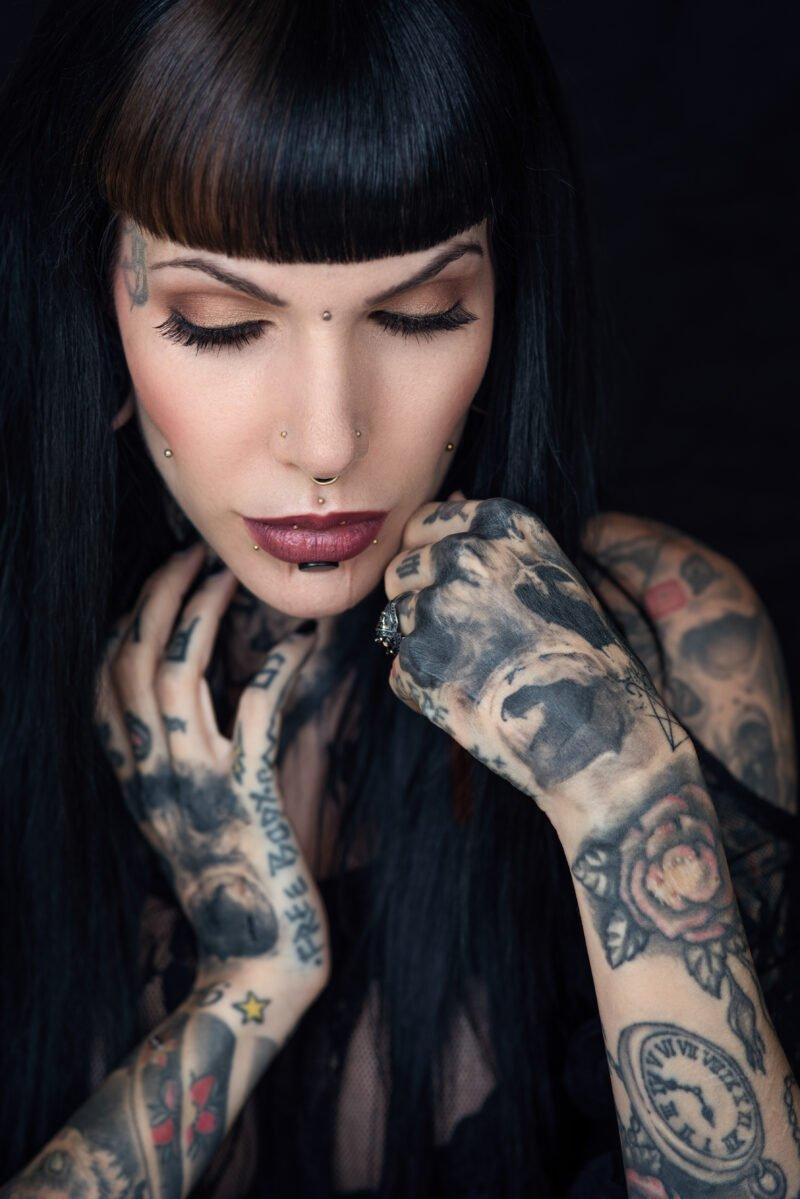 frauenportraits mit schwarzem hintergrund und tätowiertem model