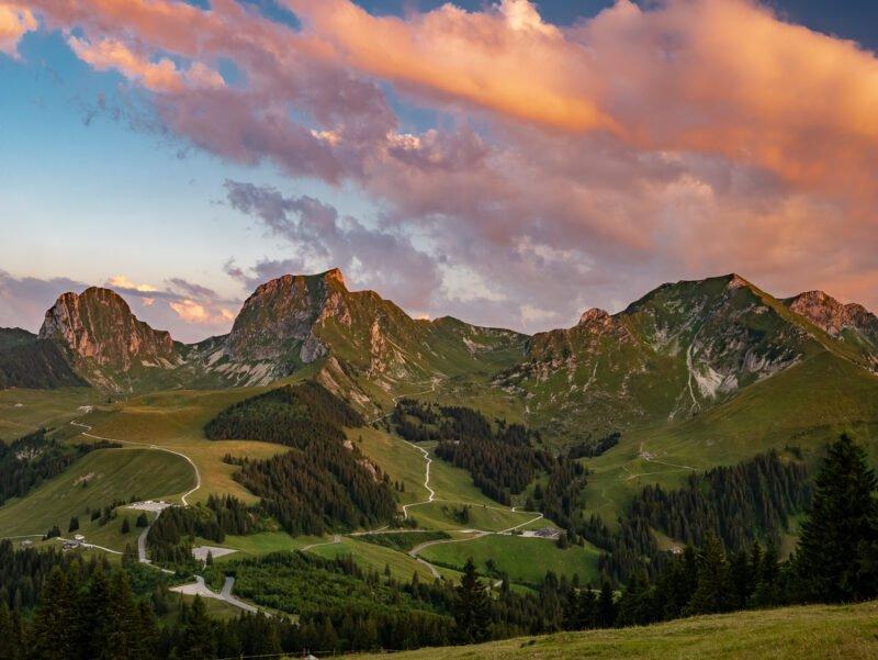 fotolocations gebirge mit gruener wiese und wolken am himmel