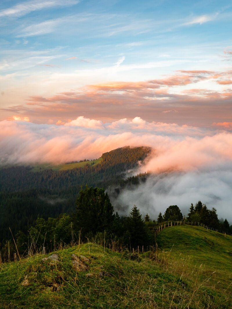 gruene huegellandschaft mit wolken bei sonnenuntergang