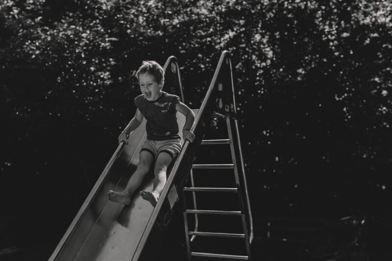 junge rutscht die rutschbahn lachend hinunter
