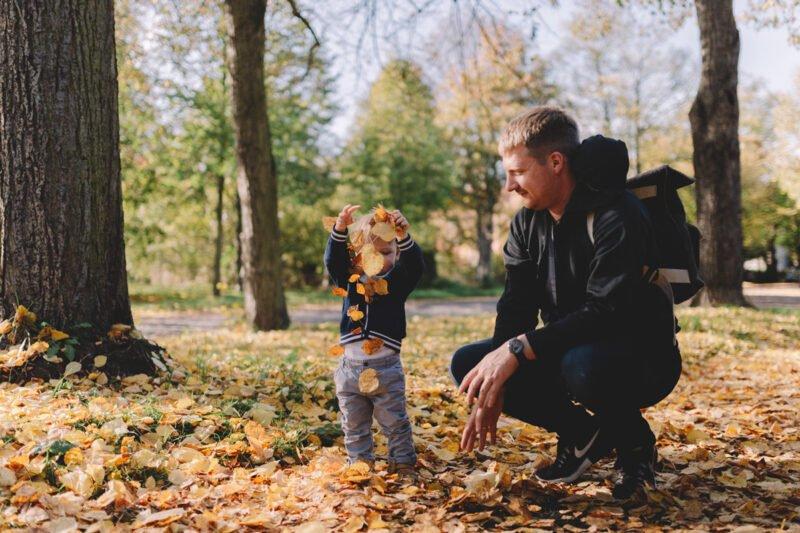 familienfotos im wald mit kind und vater spielend mit blaetter auf dem boden