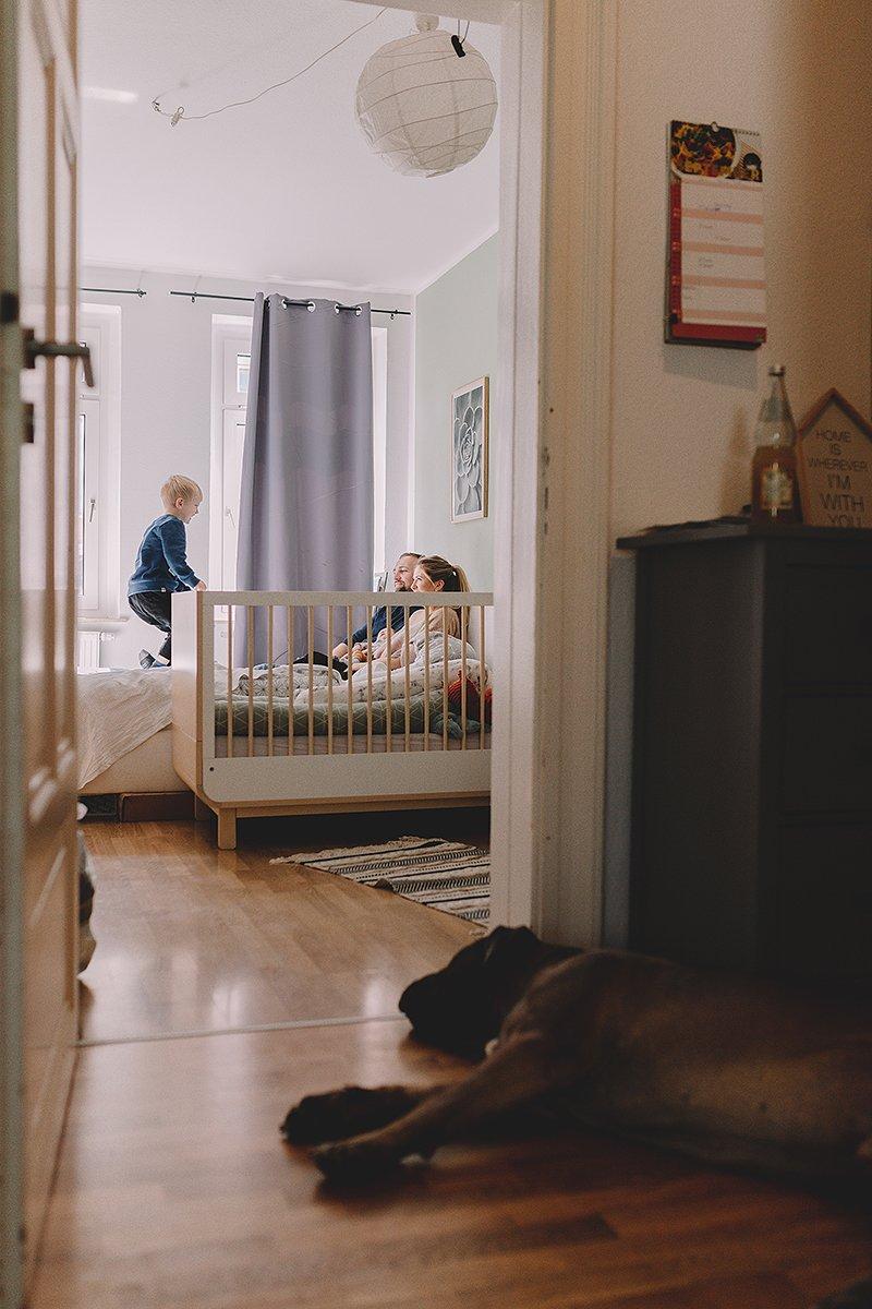 familienfotos aus dem schlafzimmer worin eltern mit kind lachend spielen