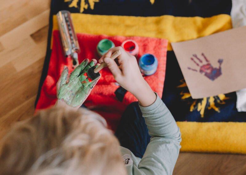 kind spielt mit malfarben an den haenden