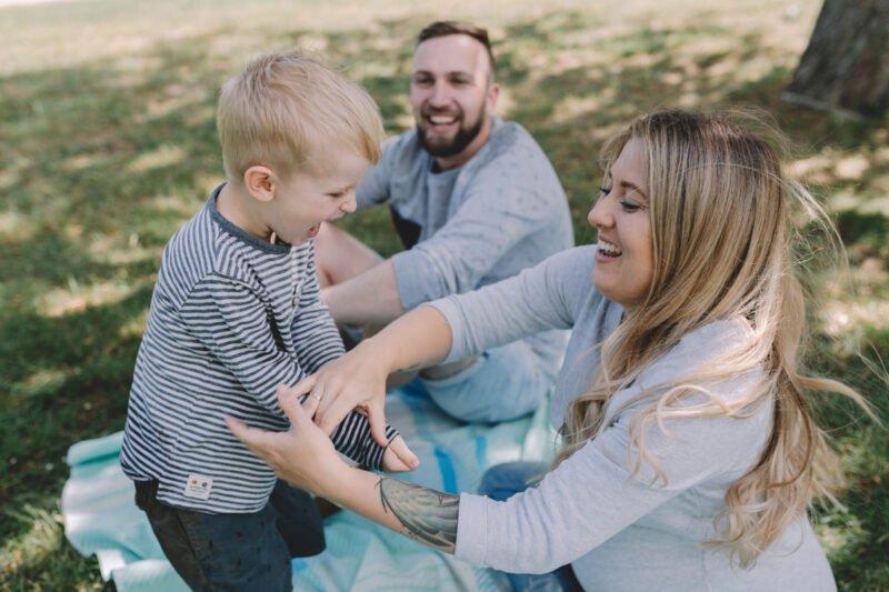 familienfotos draussen mit vater und mutter und kind lachend