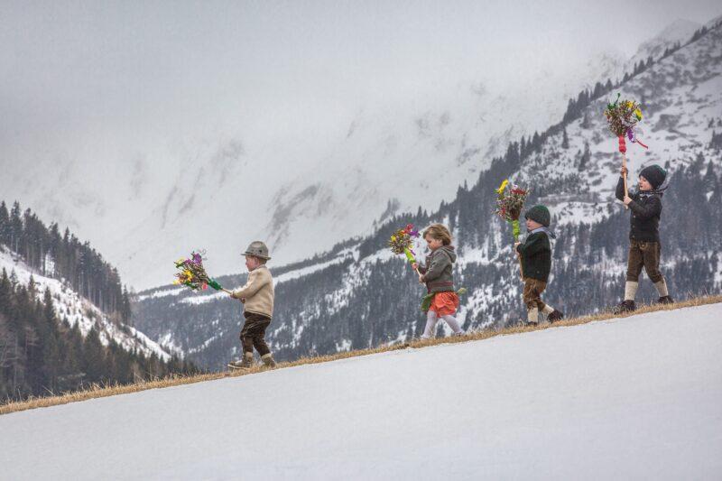 heimatfotografie von kinder mit blumenstraeussen laufen schneebedeckten huegel herunter