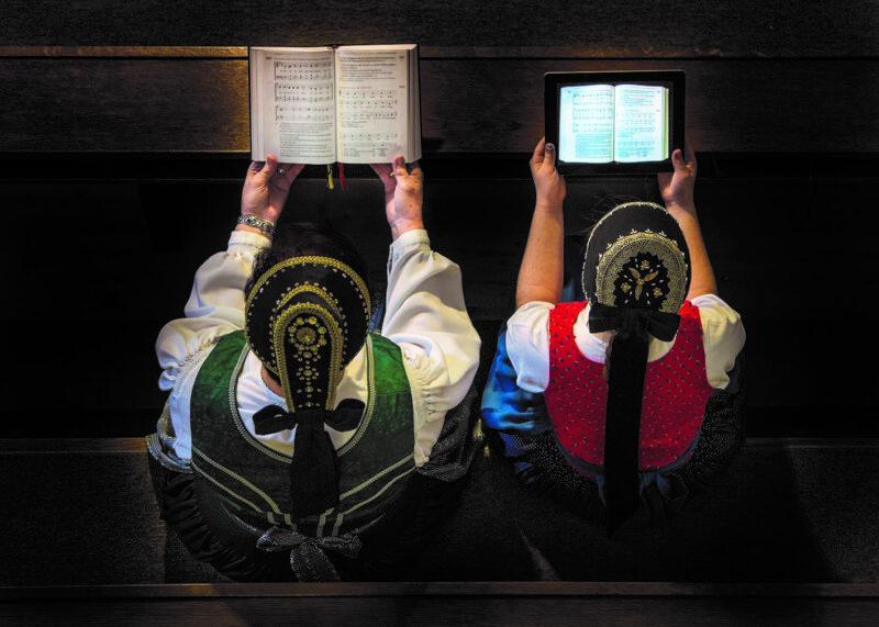 zwei menschen sitzen auf bank und einer haelt buch und eine frau haelt ein ipad in der hand