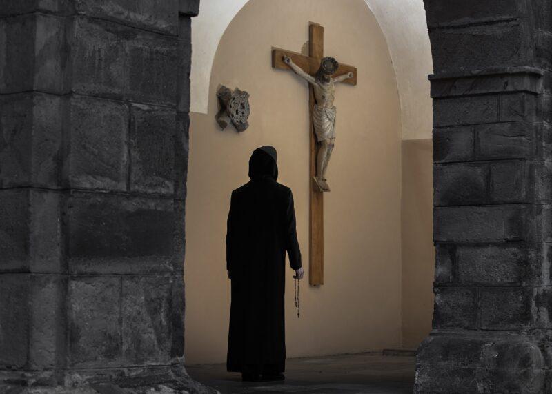 heimatfotografie von moench der in die kirche mit kreuz in der hand laeuft