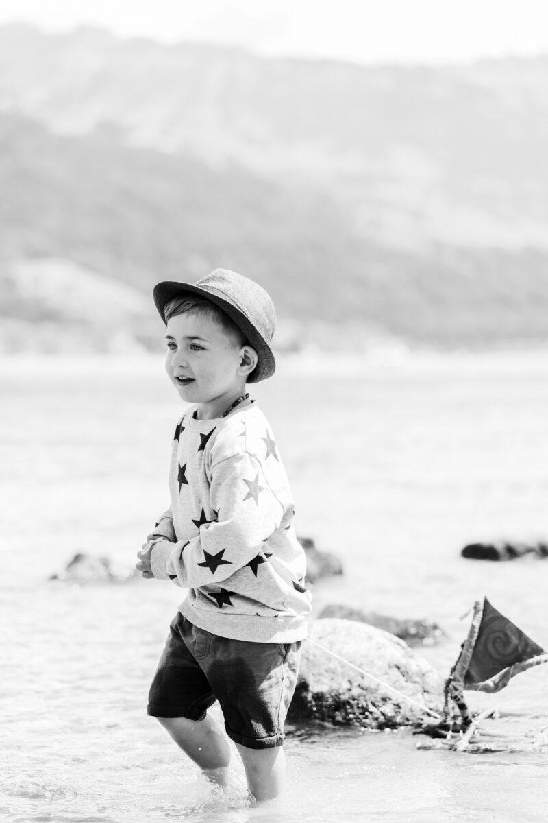 kleiner junge spielt mit holzschiff im wasser