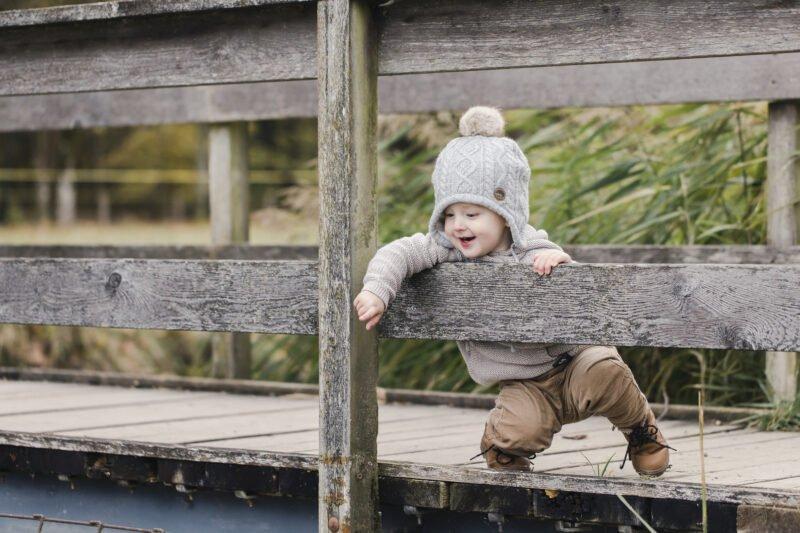kleiner junge auf holzbruecke kniet nieder und streckt arm aus