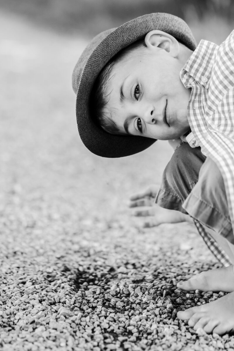 outdoorshooting mit kinder worin ein junge zur kamera schaut als schwarz-weiss foto