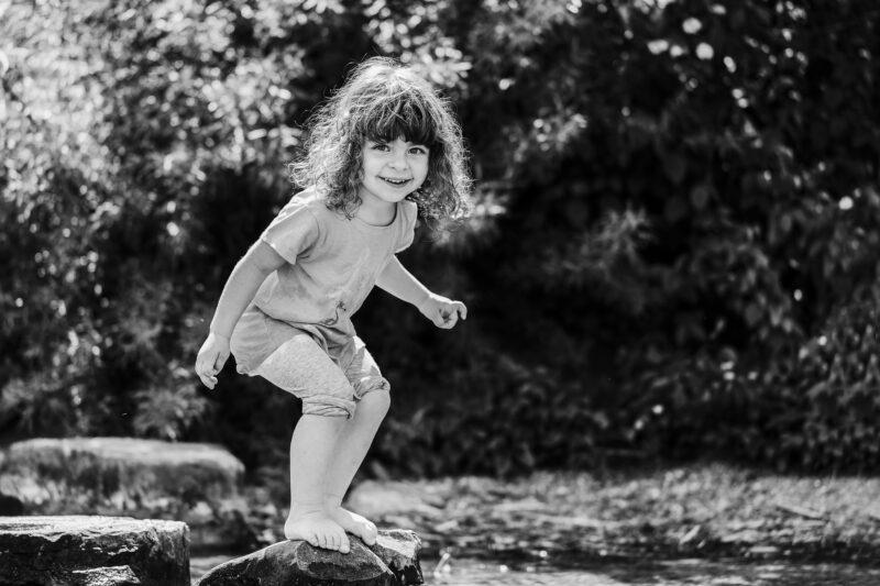 outdoorshooting mit kinder maedchen steht in der sonne und laechelt