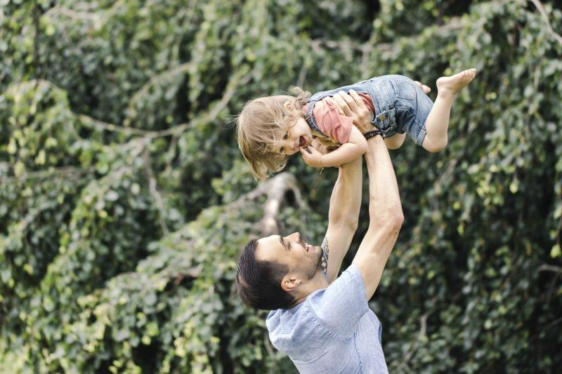 outdoorshooting mit kinder wobei vater seine tochter in die luft hebt