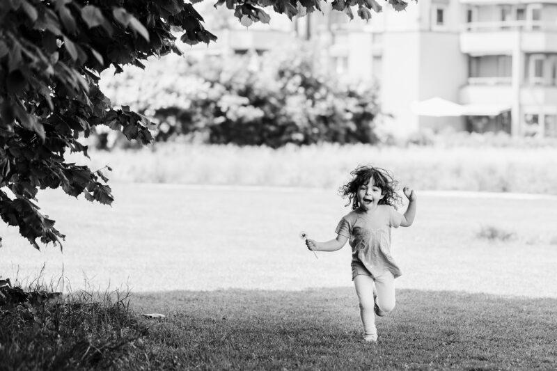 maedchen rennt ueber wiese lachend