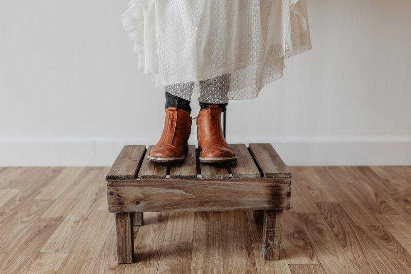 jemand steht auf braunem trittbrett mit braunen schuhen und weissem kleid