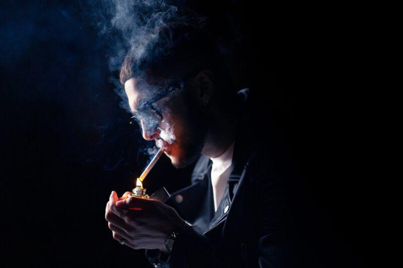Mann mit Zigarette vor dunklem Hintergrund